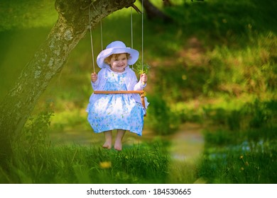 A beautiful little girl swinging in a sunny day with trees against the background