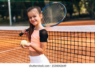 Beautiful little girl is training in a tennis club