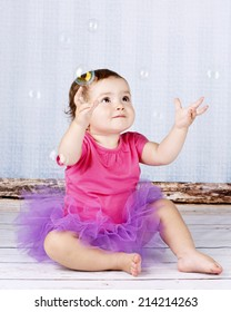 Beautiful little girl in tutu skirt playing with bubbles