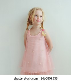 beautiful little girl with two pigtails in peach pink dress