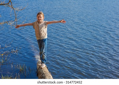 Beautiful little girl walking on trunk of tree that fell into lake.