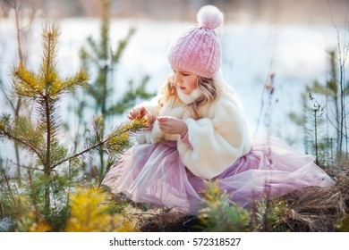 Beautiful little girl walking in sunny spring park