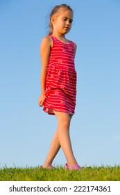 Beautiful little girl walks on green grass in summer park