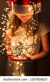 Beautiful little girl wearing Santa hat and holding bunch of Christmas lights; child setting up Christmas decorations and waiting for Santa