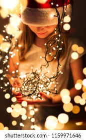 Beautiful little girl wearing Santa's hat and holding bunch of Christmas lights; child setting up Christmas decorations and waiting for Santa