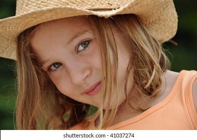 a beautiful little girl wears a cowboy hat