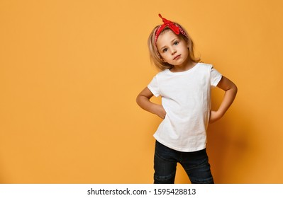 Beautiful little girl in a white T-shirt and a red bandage on her head with blue eyes looks slyly on yellow background