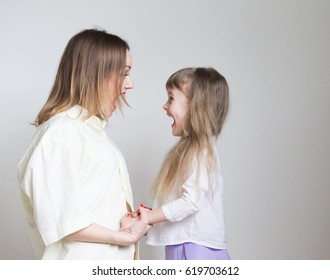 Beautiful little girl and woman, long blonde hair, pretty eyes, white shirt. Family portrait. Creative concept. Mom and daughter, relationship love