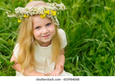 Beautiful little girl with a wreath on her head playing in a flowering field. A girl is playing in nature surrounded by yellow flowers.