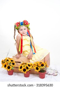 Beautiful little girl with a wreath of poppies sits on a wooden box with sunflowers in pots. Child isolated on white studio background