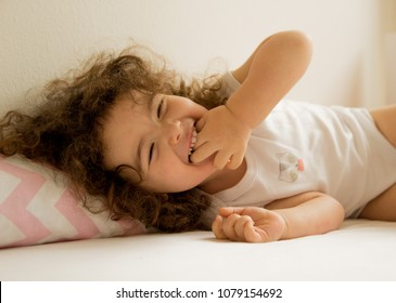 beautiful little girl, young child lying on bed laughing with pink pillows