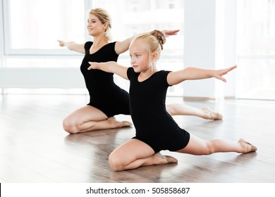 Beautiful little girl and young woman ballerina dancing together in ballet school