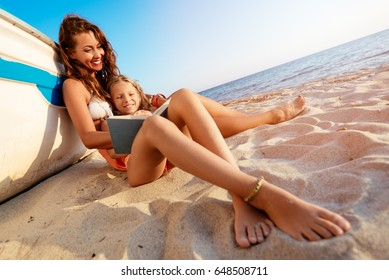 Beautiful little girl and young woman reading a book on the sandy beach. She is sitting next to boat with smile on her face.