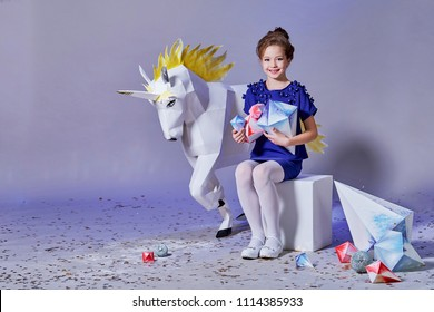 Beautiful little girl,advertising,creative decorations,holding paper diamond.White unicorn origami,character fairy tales. Child elegant blue dress,style kids.Studio,lilac background.copy space.