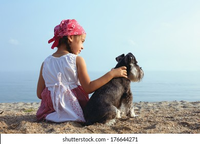 beautiful little girls embracing her dog looking at the sea