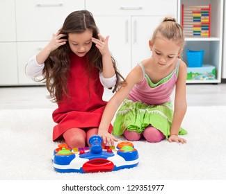 Beautiful little girls playing on the carpet