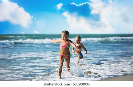 Beautiful little girls run on the seashore