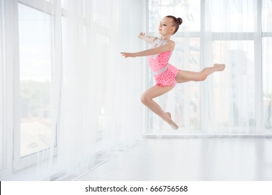 Beautiful little gymnast girl in pink sportswear dress, performing art gymnastics element, jumping, doing split leap in the air. Sport, training, stretching, active lifestyle concept