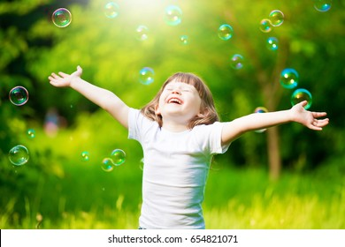 Beautiful little haired hair girl, has happy fun smiling face, pretty eyes, short hair, playing soap bubbles, dressed in white t-shirt. Child portrait. Creative concept.