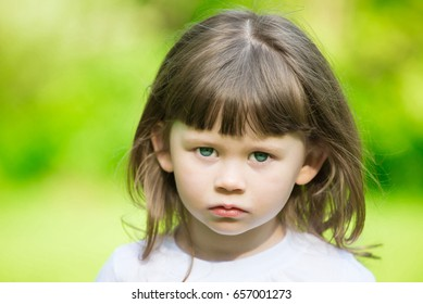 Beautiful little haired hair girl, has sad face, blue eyes, short hair, dressed in white t-shirt. Child portrait. Creative concept. Close up.