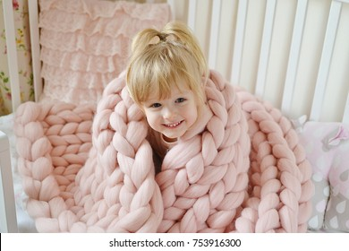 Beautiful Little Happy Blond Ginger Girl Sitting on Bed with a Pink Knitted Giant Plaid Blanket