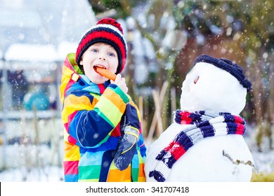 Beautiful little kid boy making a snowman and eating carrot. child playing and having fun with snow on cold day. Active outdoors leisure with kids in winter.