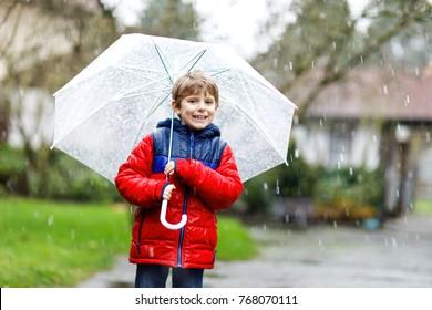 Beautiful little kid boy on way to school walking during sleet, rain and snow with an umbrella on cold day. Happy and joyful child in colorful fashion casual clothes