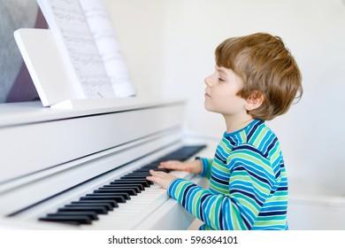 Beau petit garçon jouant du piano dans le salon ou l'école de musique. Enfant d'âge préscolaire s'amusant à apprendre à jouer de l'instrument de musique. L'éducation, le concept de compétences.