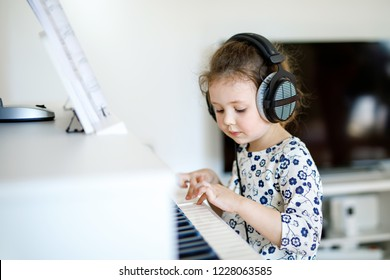 Beautiful little kid girl playing piano in living room or music school. Preschool child having fun with learning to play music instrument. Education, skills concept