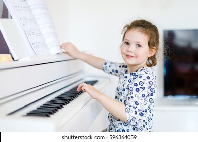 Beautiful little kid girl playing piano in living room or music school. Preschool child having fun with learning to play music instrument. Education, skills concept.