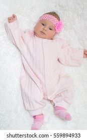 beautiful little kid with a pink bandage on a head lies on a white plaid with raised hand