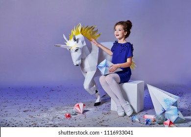 Beautiful little lady girl, fabulous unicorn near. Child elegant blue dress.  Fashion kid, advertising shop, purple, lilac background, copy space..