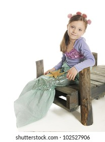 A beautiful little mermaid sitting on a rustic wood dock.  On a white background.