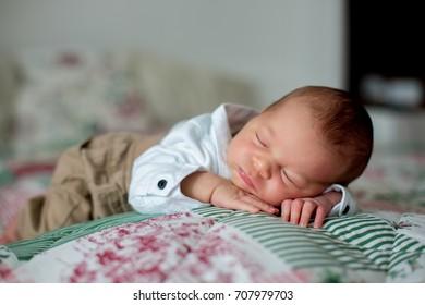 Beautiful little newborn baby boy, dressed as little gentlemen, sleeping in bed, cute toy next to him