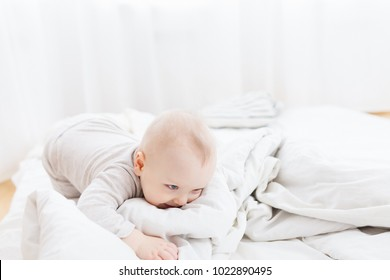 Beautiful little positive baby playing on the bed wrapped up in cozy blankets. White light interior