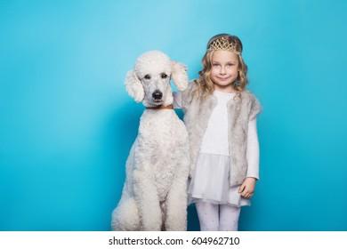 Beautiful little princess with dog. Friendship. Pets. Studio portrait over blue background