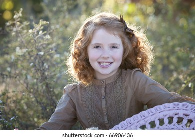 Beautiful little redheaded girl outdoors in afternoon light in meadow