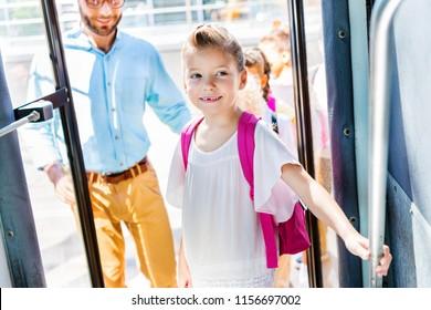 beautiful little schoolgirl entering school bus with teacher and classmates on background