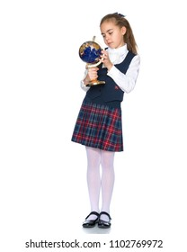 Beautiful little schoolgirl girl studying a globe on a white background. The concept of teaching geography in school, travel. Isolated.