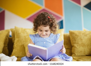 Beautiful little smiling girl with dark curly hair in blue dress reading child book on sofa at home