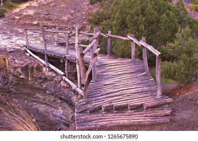 Beautiful little wooden bridge from logs with fence trough break, precipice, abyss, green juniper trees, ground, stones