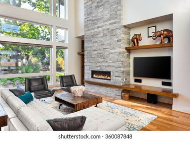 Beautiful living room with hardwood floors and fireplace in new luxury home. Has very tall vaulted ceiling and bank of windows, along with floor to ceiling fireplace and beautiful green plants outside
