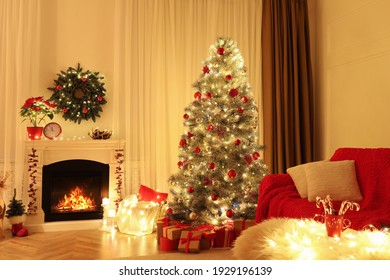 Beautiful living room interior with burning fireplace and Christmas tree in evening