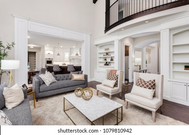 Beautiful living room interior with hardwood floors and fireplace in new luxury home. Has view of kitchen,hallway, and loft area.