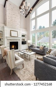 Beautiful living room interior with hardwood floors and fireplace in new luxury home. Large bank of windows with exterior view.