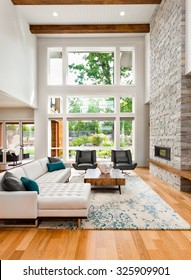 Beautiful living room interior with hardwood floors, huge bank of windows, tall vaulted ceiling, and fireplace in new luxury home