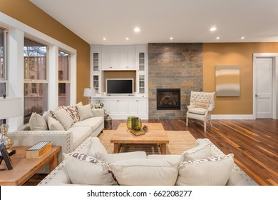 Beautiful living room interior with hardwood floors and fireplace in new luxury home. Couches at Right angles surround coffee table and fireplace with floor to ceiling stone surround.