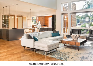Beautiful living room interior in new luxury home with view of kitchen. Home interior with hardwood floors and open floor plan showing dining room, kitchen, and living room. Has high vaulted ceilings.