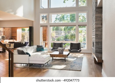 Beautiful living room interior in new luxury home with view of outdoor covered patio. Home interior with hardwood floors and open floor plan with vaulted ceilings
