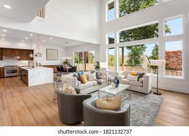 Beautiful living room and kitchen interior in new modern luxury home with large bank of windows showing exterior view. Features open concept floor plan, waterfall island, stainless steel appliances
